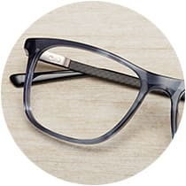 Slate blue acetate glasses #4435316 with carbon fiber temple arms folded on top of a light wood tabletop.