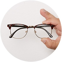 Hand holding browline glasses # 1912039 in black with red floral pattern.