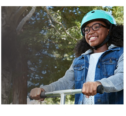 Young girl smiles while riding a scooter outside wearing medium-sized Dare square glasses #4440616 in blue tortoiseshell from the Style Squad kids' collection with Blokz Trivex lenses and light blue helmet.