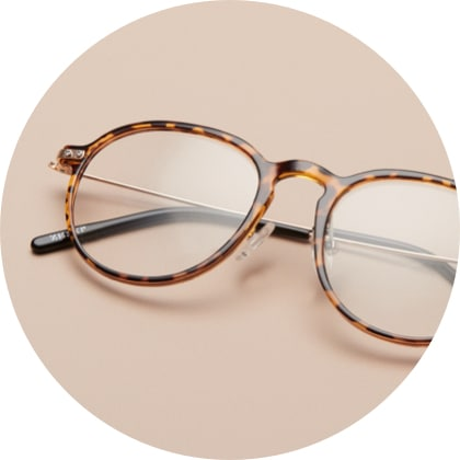 Zenni round glasses #7822625 in tortoiseshell, on a brown background.