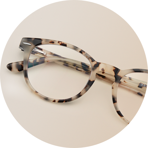 Ivory tortoiseshell round glasses #109835 on a brown background.
