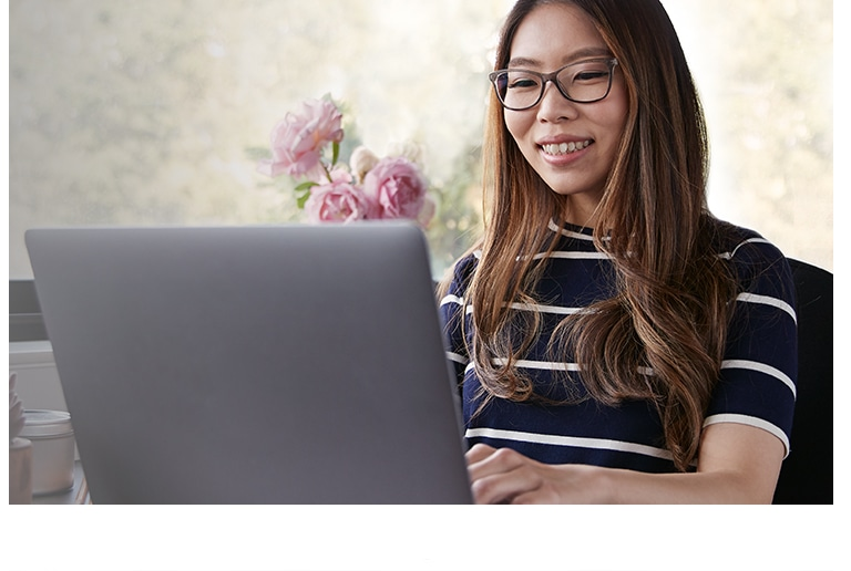 A young woman with long brown hair wearing Blokz by Zenni blue blocker glasses smiles while using her laptop computer.