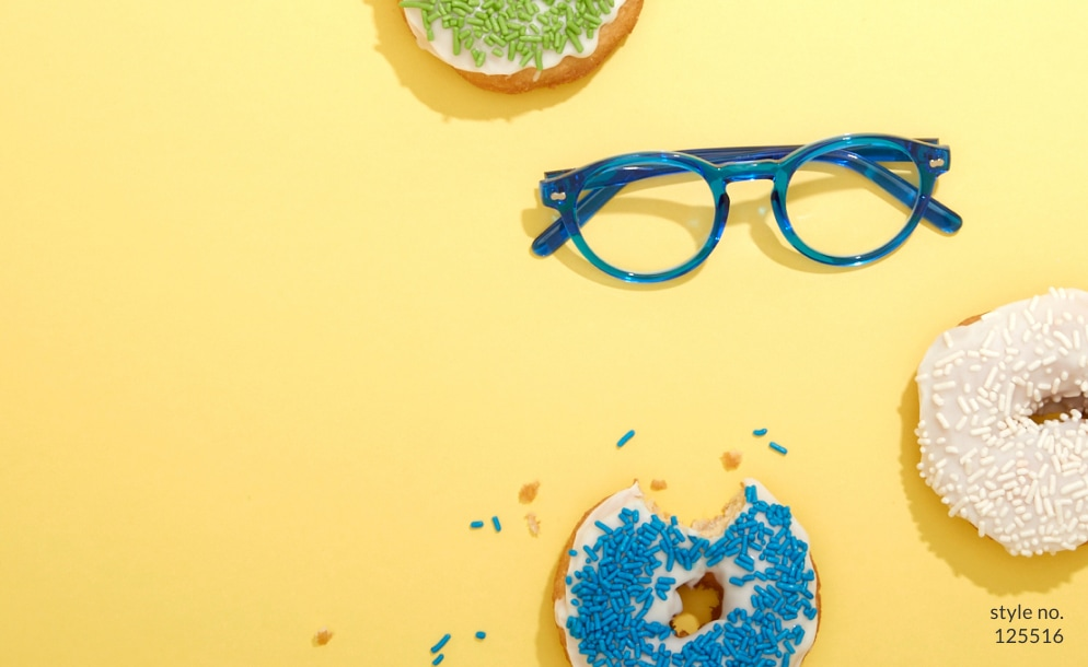 Image of a pair of Zenni round glasses #125516 against a yellow background, surrounded by three sprinkled donuts.