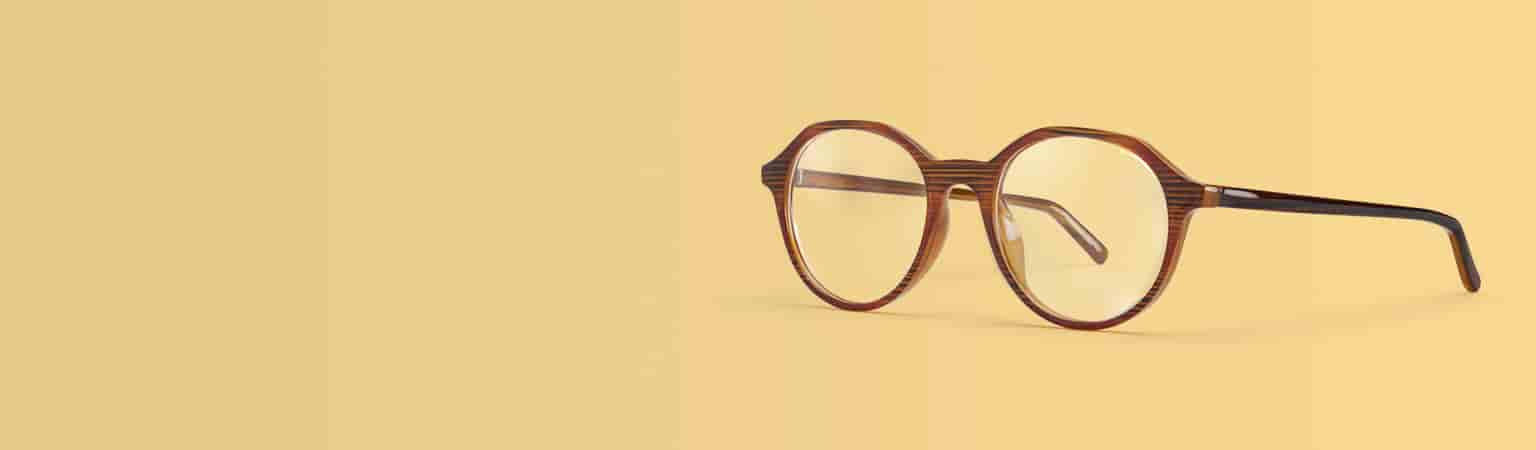 Zenni round glasses #2030715 in brown with subtle woodgrain pattern against a yellow background.