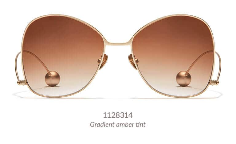 Make a bold statement in these fashion-forward butterfly sunglasses. The wide metal frame has an oversized silhouette, and the unique temple arms are positioned on the bottom of the frame and feature metal balls on the tips. Shown in gold with gradient amber tint.