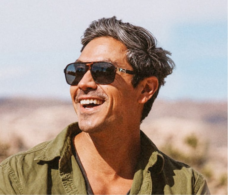 Man wearing khaki green jacket and sunglasses smiles towards the sun with Joshua Tree National Park in background.