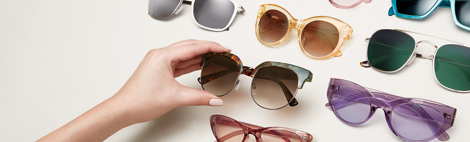 Hand grabbing a pair of premium browline sunglasses from an array of fashionable sunglasses.