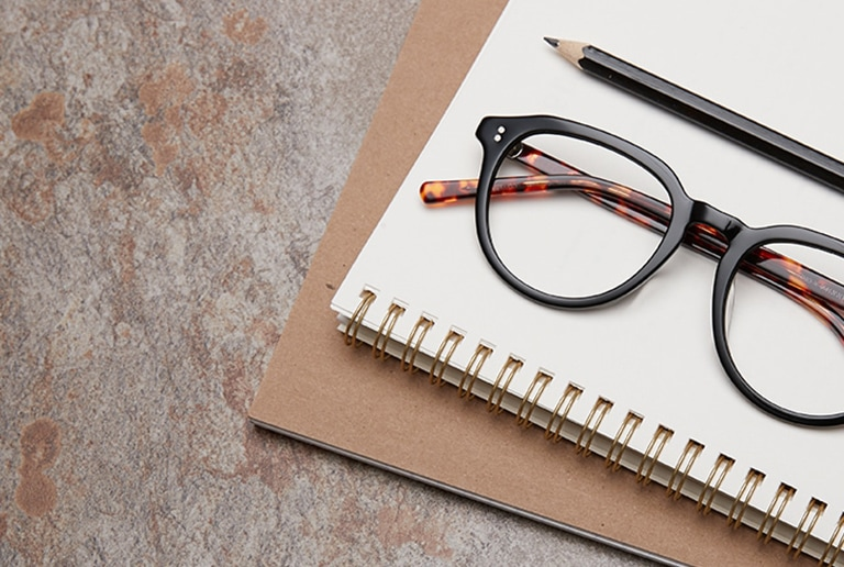 Spree round acetate glasses #4432921 from the Timo x Zenni Out of Office collection in black with tortoiseshell temple arms folded on top of a spiral bound notebook with pencil.