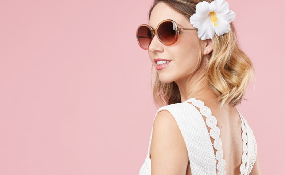 Zenni premium round sunglasses #1117624 in watermelon, worn by a lady wearing a white top with a white flower in her hair, on a pink background.