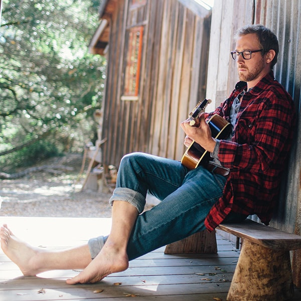 A young, bearded man in a red plaid shirt and Zenni eyeglasses leans against a cabin, strumming an acoustic guitar