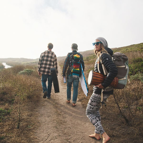 A young, bearded man in a red plaid shirt and Zenni eyeglasses leans against a cabin, strumming an acoustic guitar. A woman in sunglasses with a backpack and bongo walks on a beach trail behind two men with a guitar and surfboard.