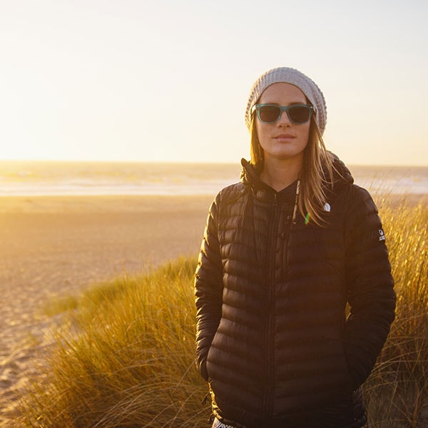 A young woman in a knit hat, black down jacket and Zenni sunglasses stands with the beach behind her at sunset.