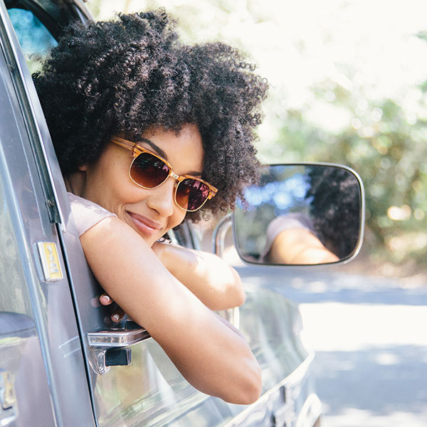 A smiling woman with kinky curls wears retro browline sunglasses from Zenni, hanging out the passenger side window.