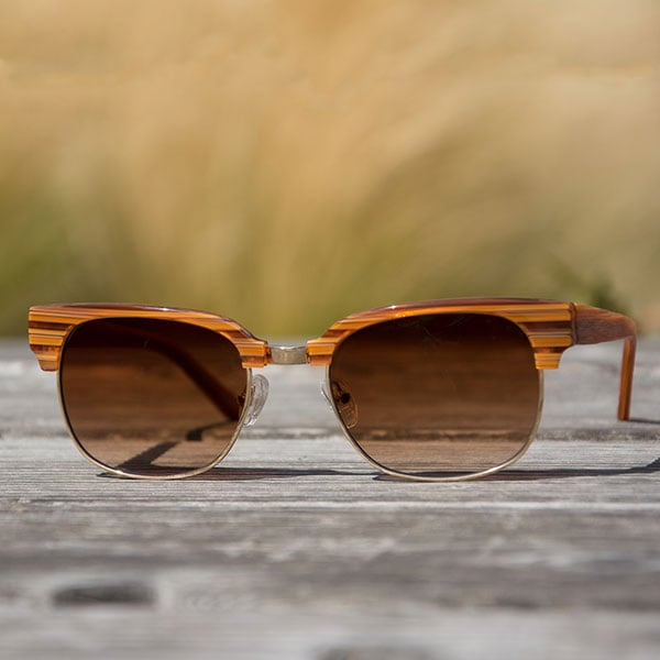 The Tiburon browline sunglasses from Zenni are shown close-up on a wood table with beach grass in background.