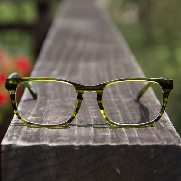 The green-striped Inverness eyeglasses from Zenni are pictured up close on the end of a weathered wood plank.