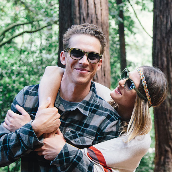 In a redwood grove, a young woman with a headband and Zenni sunglasses embraces a man with sunglasses from behind.