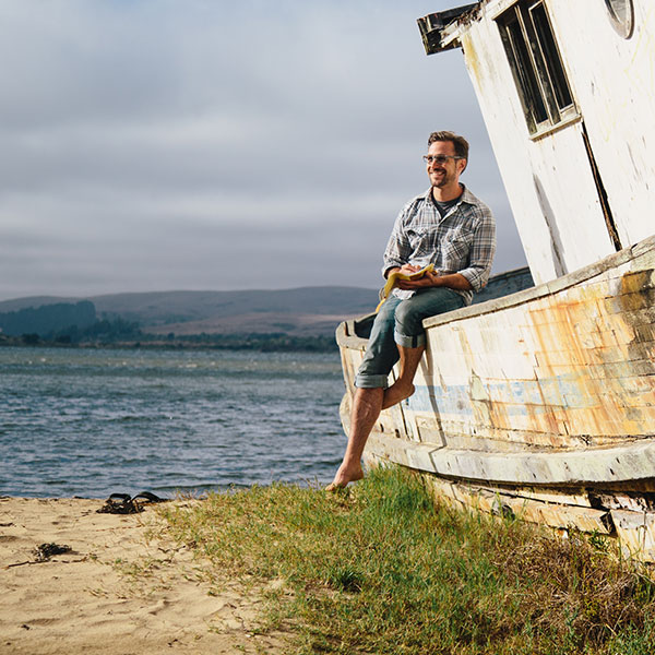 A young man wearing Zenni sunglasses sits on the edge of a rusty, beached fishing boat by the sea, journaling.
