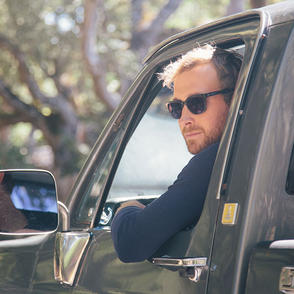 A blonde, bearded man wearing green Sausalito square sunglasses from Zenni leans out the driver side of a pickup.