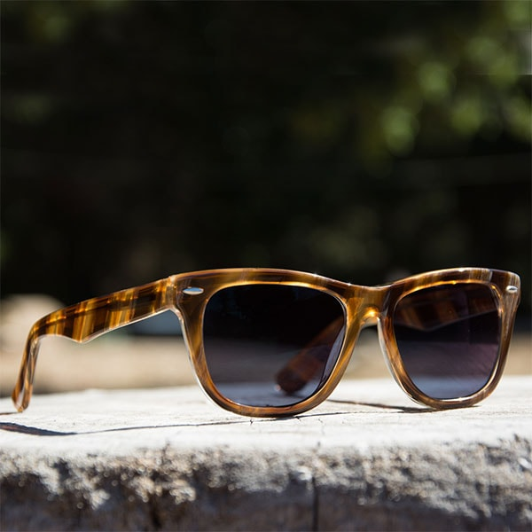 The glossy, brown-striped Bodega square sunglasses from Zenni are pictured close-up on a stone ledge.