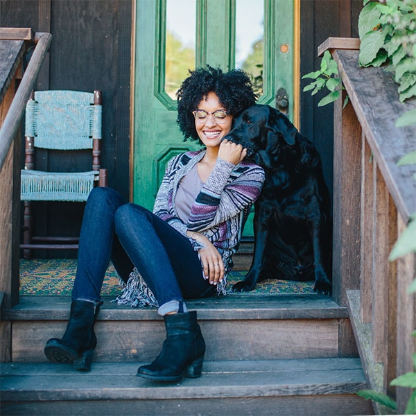 A smiling woman with kinky black curls and Zenni eyeglasses sits on rustic porch steps with a black lab.