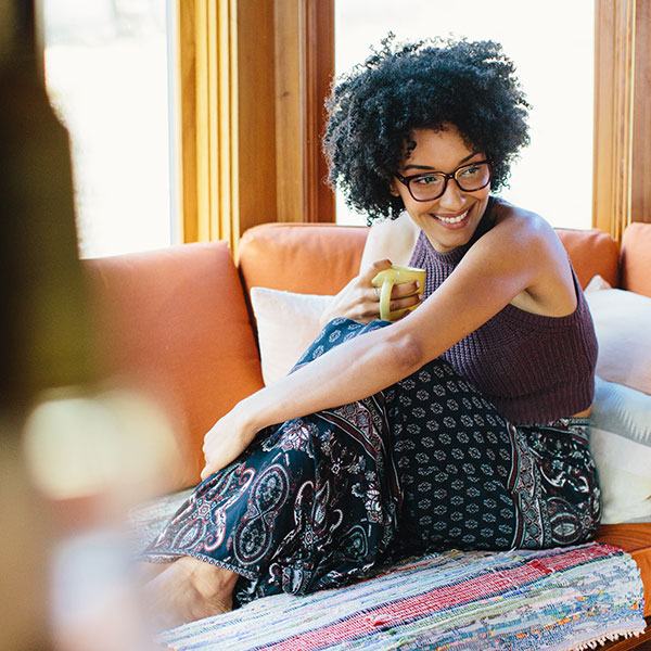 A smiling, bohemian chic woman with kinky black curls and Zenni eyeglasses lounges with a cup of tea.