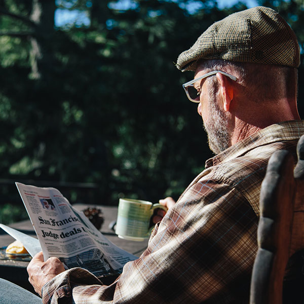 A gray-bearded man in a tweed cap and Zenni sunglasses sits outside enjoying his coffee and newspaper.