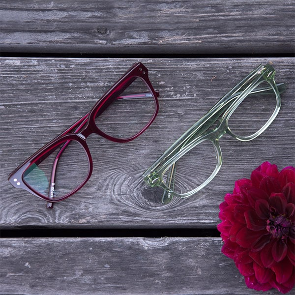 Red Sausalito eyeglasses and translucent green Tamalpais eyeglasses from Zenni are shown up close on weathered wood with a red dahlia.