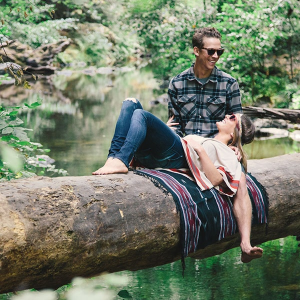 woman reclines on a guy's lap atop a blanket on a large log suspended over a creek in the redwoods.