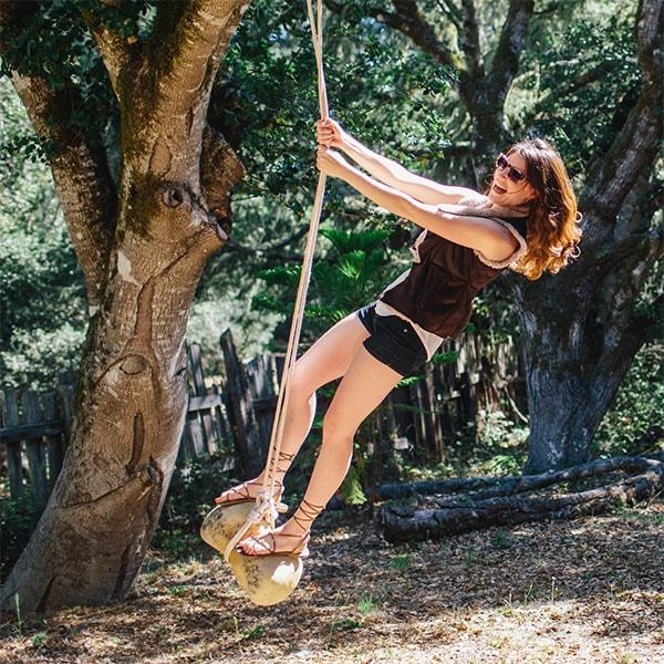 A woman wears a vest, shorts, strappy sandals and Alamere sunglasses from Zenni, smiles while swinging on rope swing in a woodsy yard.