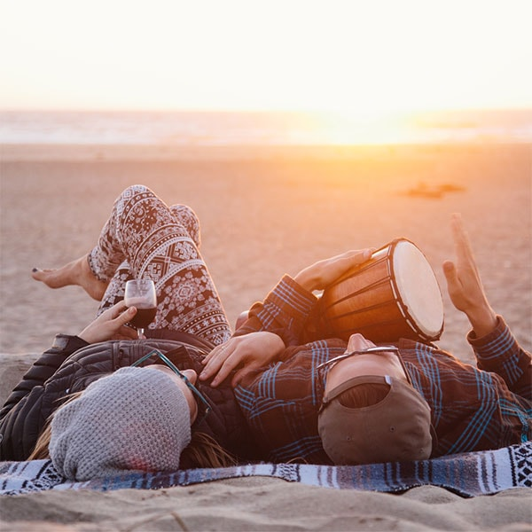 A warmly dressed couple lies on the beach at sunset. She holds a glass of red wine and he plays a bongo.