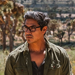 A young man wearing desert collection zenni glasses