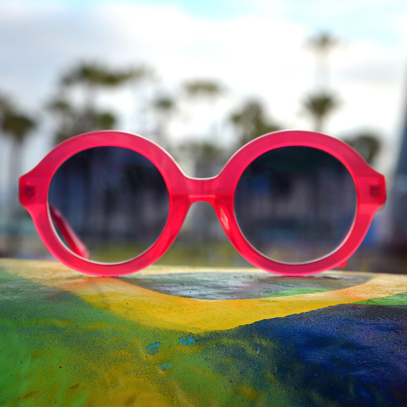 Pico round acetate sunglasses in vibrant pink with gradient gray lenses.