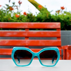 Mulholland geometric acetate sunglasses in aqua blue with gradient gray tint and Pico round acetate sunglasses in vibrant pink with gradient gray tint.