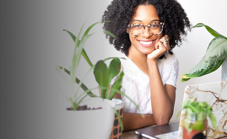 Image of a woman wearing Zenni ivory tortoiseshell square glasses #7815335 sitting by a desk with a laptop surrounded by plants.
