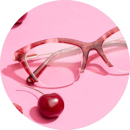 Zenni rubellite cateye glasses #7822818 with some cherries next to it on a pink background.
