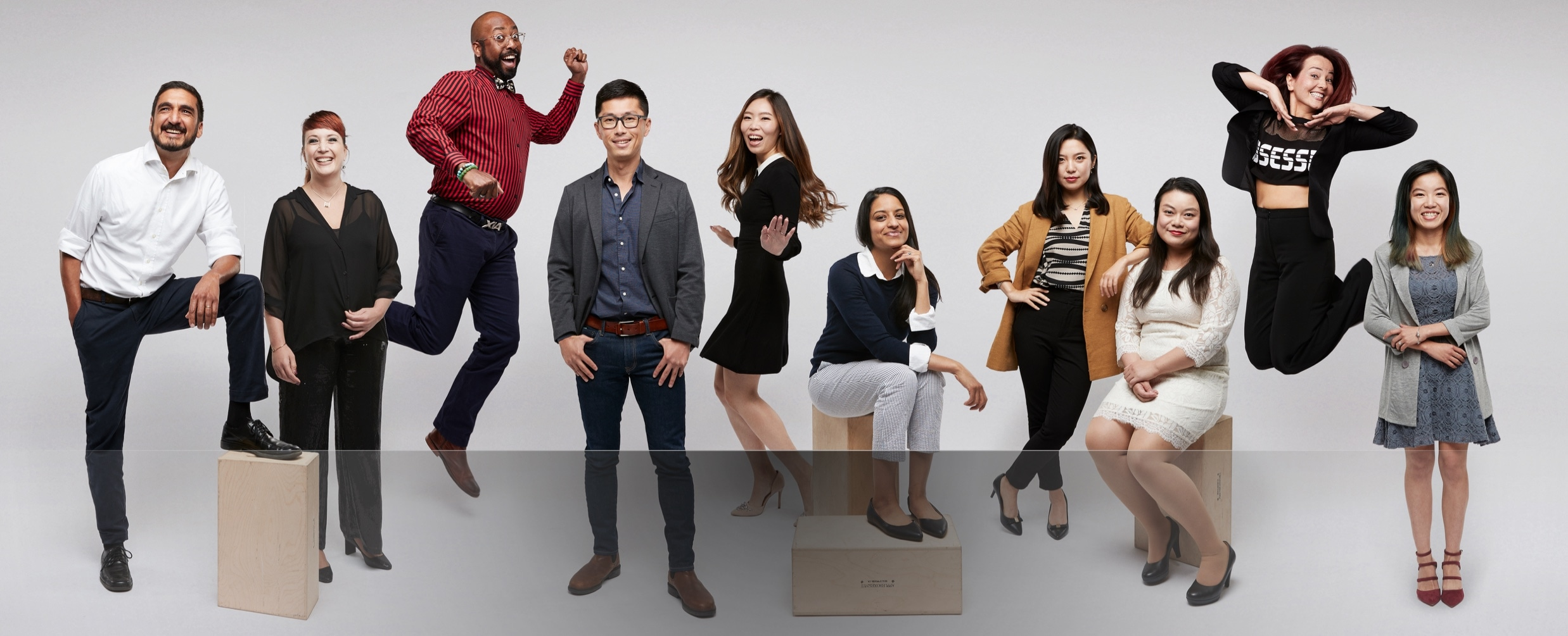 Exuberant Zenni employees striking poses against a white background.
