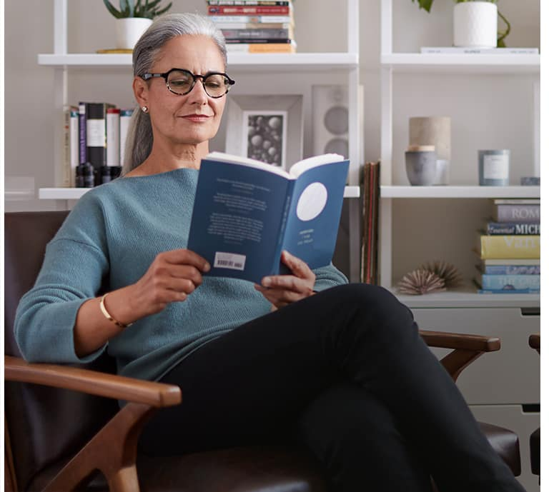Older woman wearing glasses, reading a book