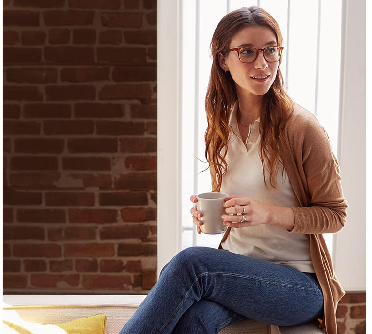 Woman wearing glasses, holding cup of coffee